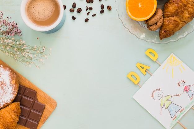 コーヒーとデザートの近くに横たわる父のための画像