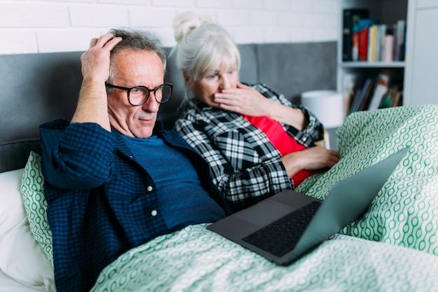 ショックを受けた高齢者のカップル、ベッドでノートパソコン