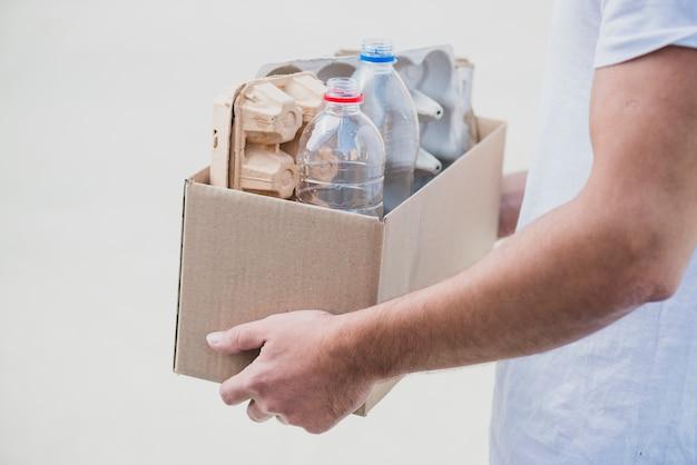 白い背景で卵カートンとプラスチックボトルとリサイクルボックスを保持する手のクローズアップ