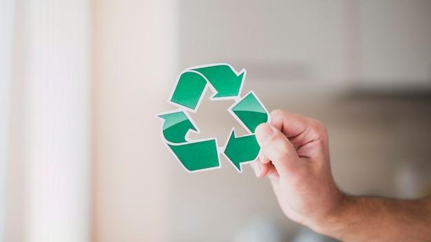 緑色のリサイクルアイコンを持つ男の手のクローズアップ