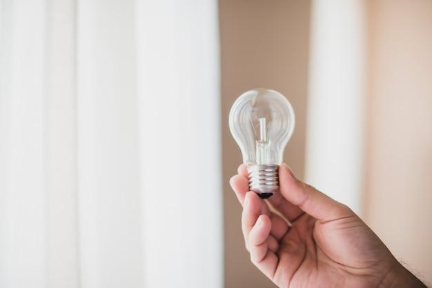 透明な電球を持つ男の手のクローズアップ