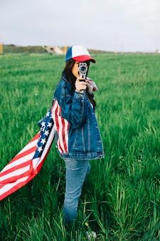 フィールドに滞在するレトロカメラ付きの少女