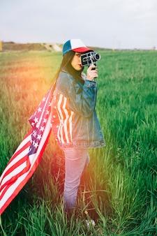 レトロなカメラを身に付けているカジュアルな服の女性