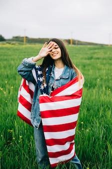フィールドに滞在しているアメリカの旗を持つ若い女性