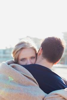 Пара обнимает под одеялом