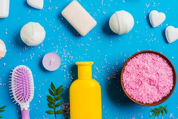 ヒマラヤの塩の俯瞰図。青い背景に石鹸とヘアブラシ