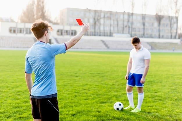 Неопознаваемый рефери, показывающий красную карточку молодому спортсмену