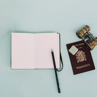 ノートブックの近くの双眼鏡とパスポート