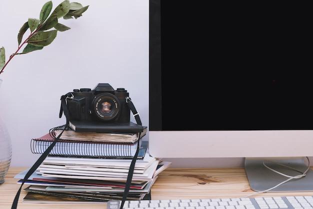コンピュータの近くのカメラとノート