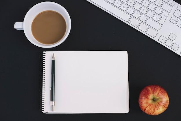ノートやキーボードの近くのコーヒーとリンゴ