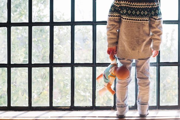 人形で窓の前に立っている女の子