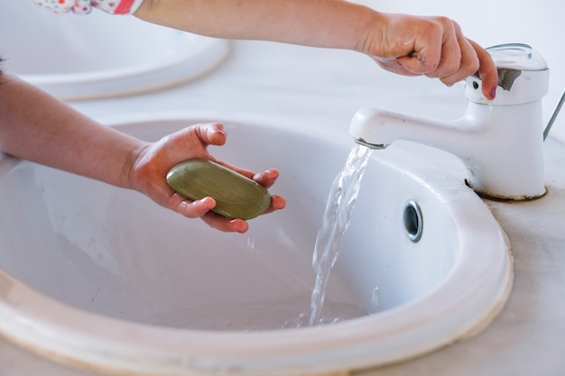 Девушка держит мыло, моет руку в раковине