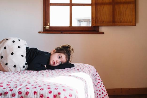 ベッドルームにベッドに横たわっているかわいい女の子