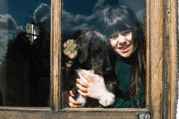 ガラスのドアを見ている彼女の犬の女の子