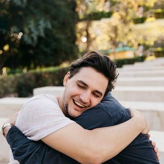 Радостный отец и сын обнимаются