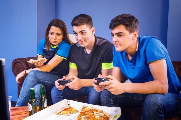 Друзья едят пиццу и смотрят футбол