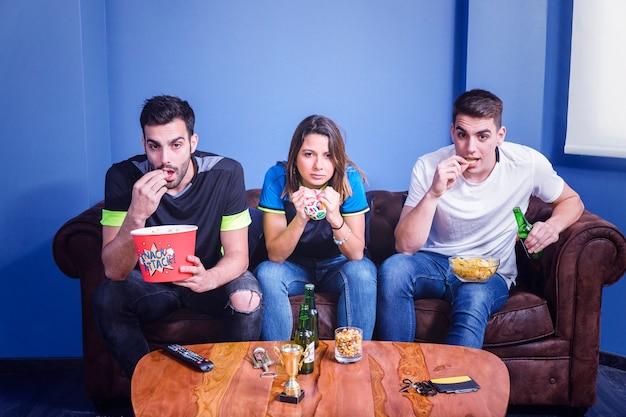 Друзья смотрят футбол с попкорном