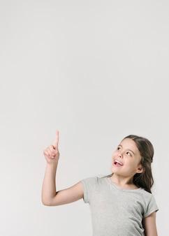 スタジオで上を指している甘い少女