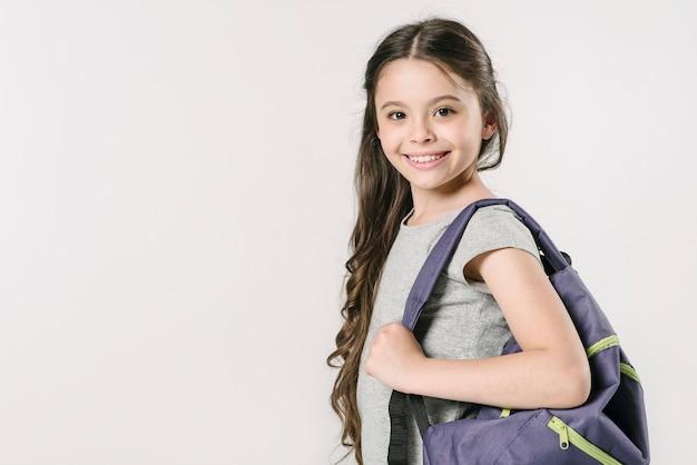 Девушка, стоящая с рюкзаком в студии