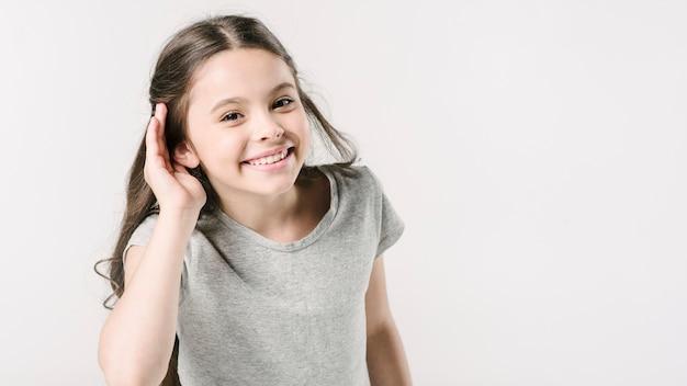 Симпатичная девушка в студии, показывая знак слушания