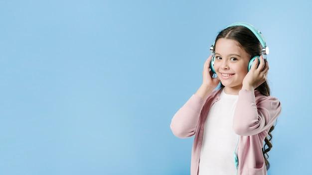 スタジオでヘッドフォンで音楽を聴く少女