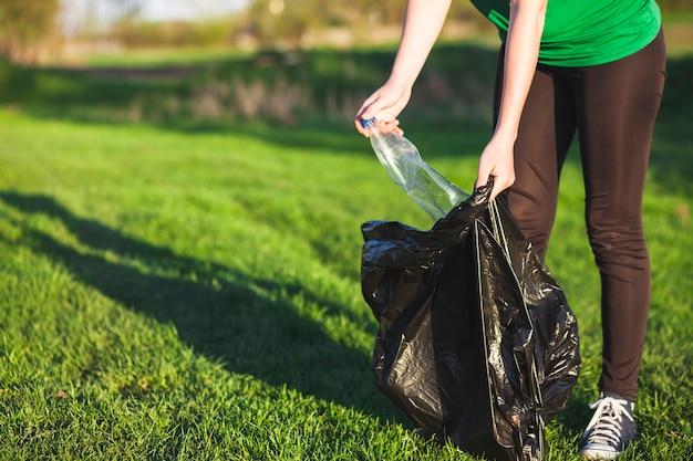 女性がゴミを集めるコンセプトをリサイクル