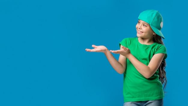 Девушка в шапке, указывая руками в студии