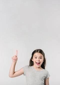 Симпатичная девушка улыбается пальцем вверх в студии