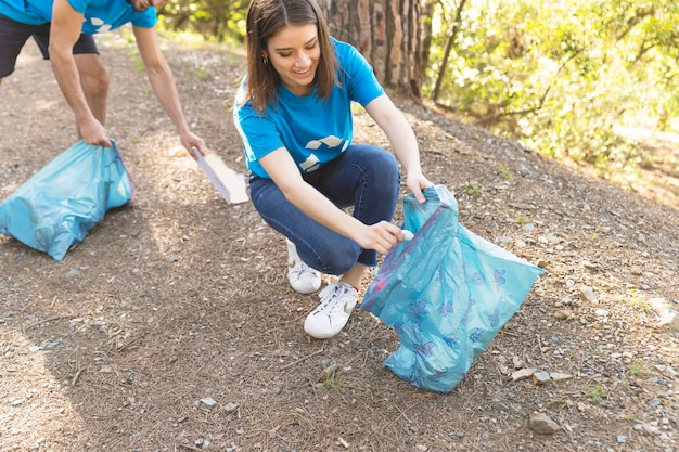 森林のゴミを集める若い女性