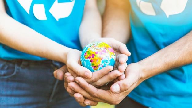 一緒に手で地球儀を保持するカップル
