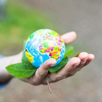 Концепция рука с листьями и земной шар