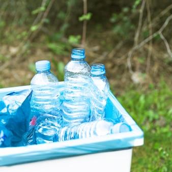 Трашкан с пластмассовым мусором на открытом воздухе