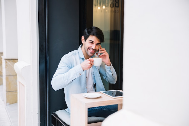 スマートフォンで話すカップを持つ笑顔の男