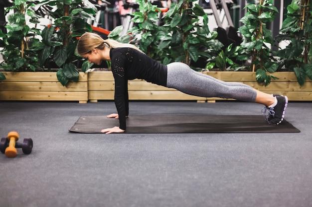 運動のマットのプッシュアップをしている女性の側面図