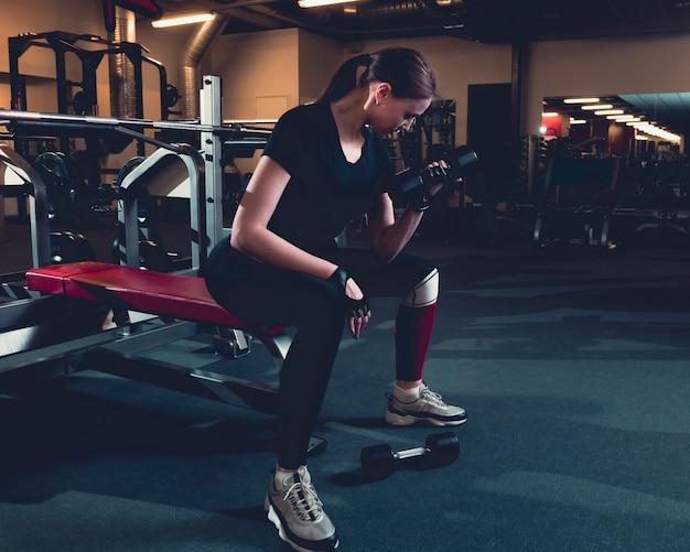 Подходящая женщина делает упражнения на бицепс с гантелями в фитнес-центре