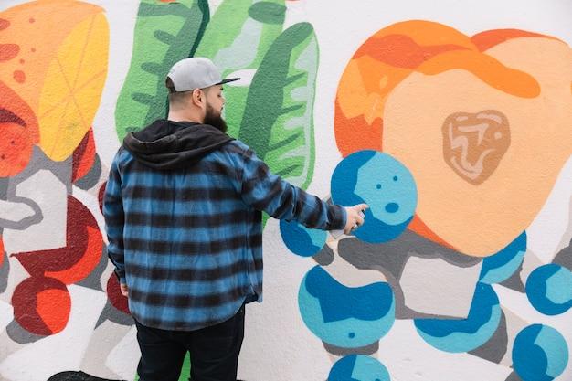 壁に落書きを描く男