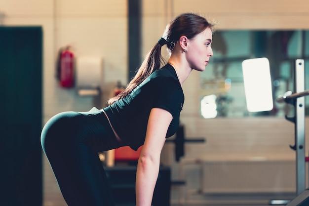 Боковой вид женщины, тренирующейся в тренажерном зале