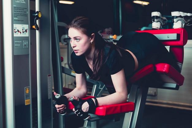 Спортивная женщина делает фитнес-упражнения в тренажерном зале