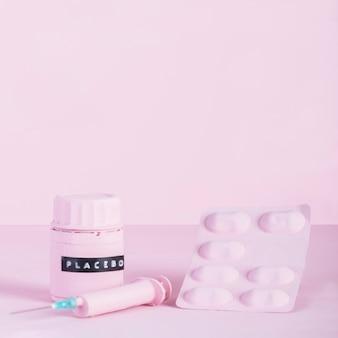 ピンクの背景にシリンジ、ピルブリスター、プラセボ瓶
