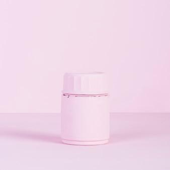 ピンクの背景にピンクの閉じた瓶