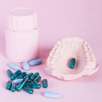 ピンクの背景にびんと義歯を入れたカプセルと丸薬