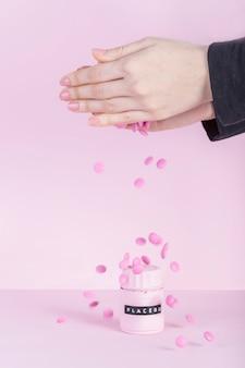 ピンクの背景の上にプラセボの瓶の上にピンクのピルが落ちる女性の手