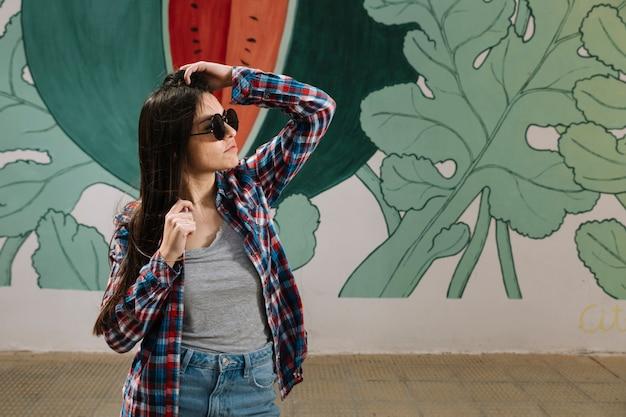 スタイリッシュな若い魅力的な女性は、落書きの壁の前に立って