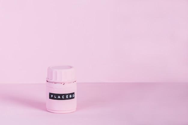 ピンクの背景に対してラベル付きプラセボ瓶