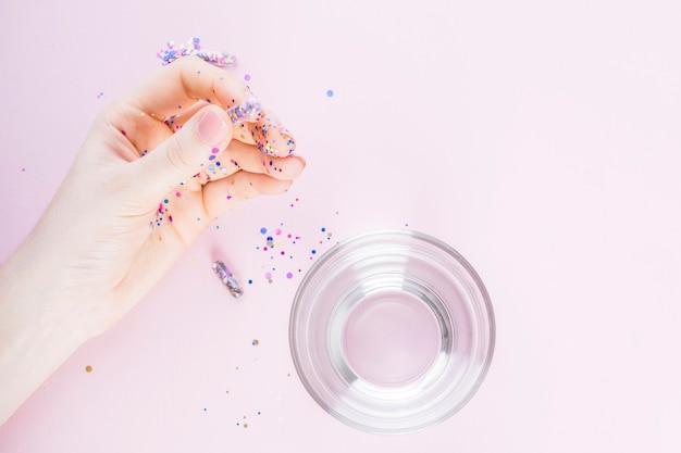 Человеческая рука с прозрачной капсулой, наполненной конфетти, кроме стекла на воде