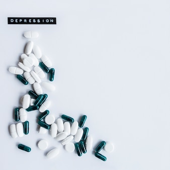 Капсулы и таблицы с меткой депрессии на белом фоне