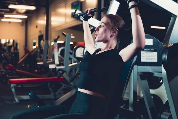 肩のプレス機で運動する女性の側面図