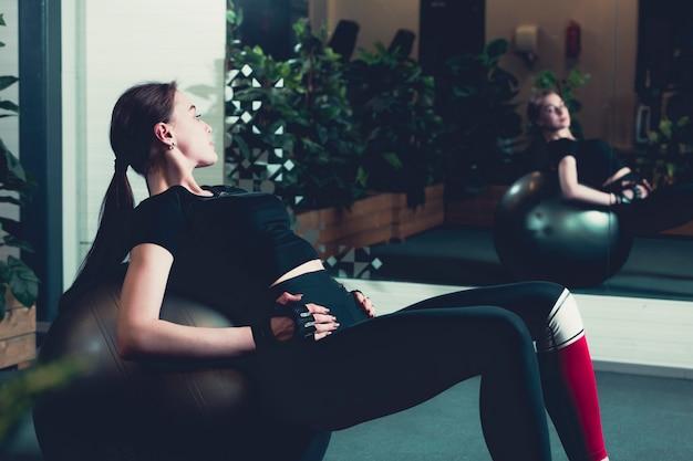 ジムのエクササイズボールで腰を上げている女性