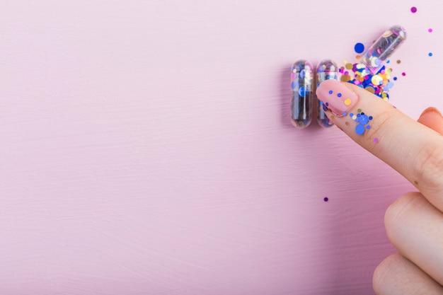 人間の指、ピンクの背景にスパチュラカプセルに触れる