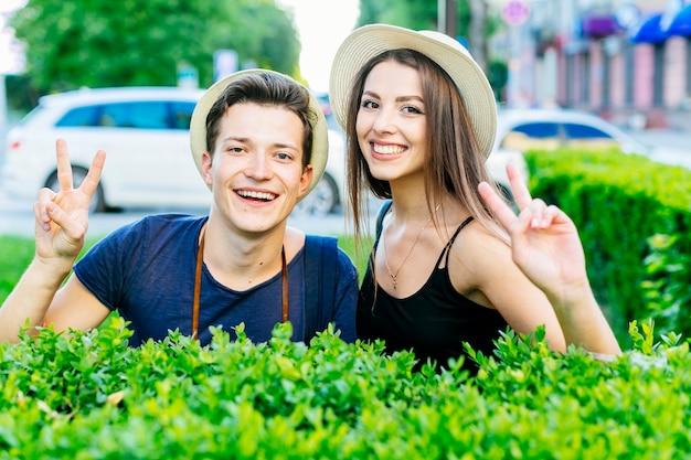 Туристическая пара делает знак мира